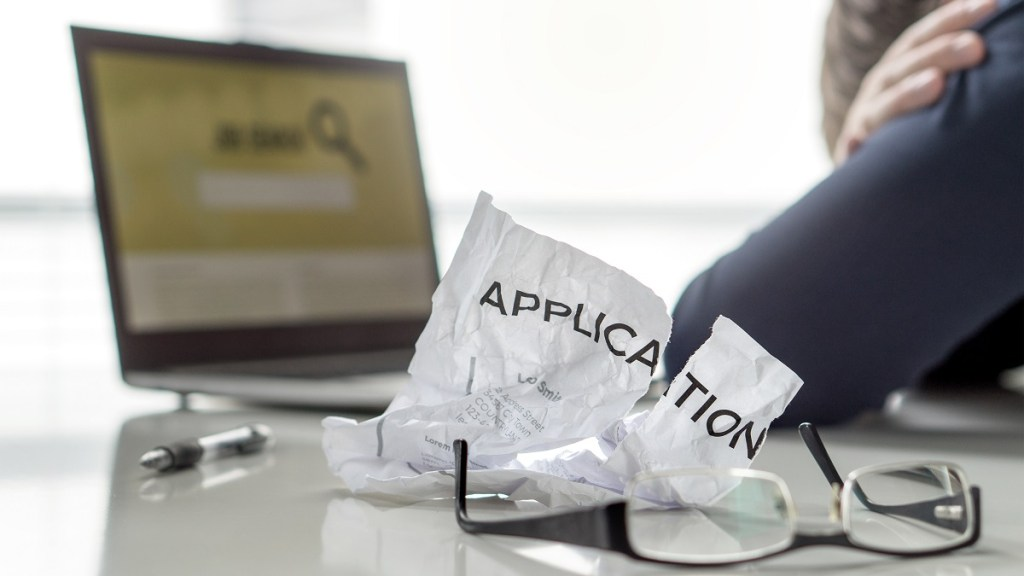"""Person with head in hands in front of computer searching for jobs. Crumpled piece of paper with the word """"application"""" next to the person."""