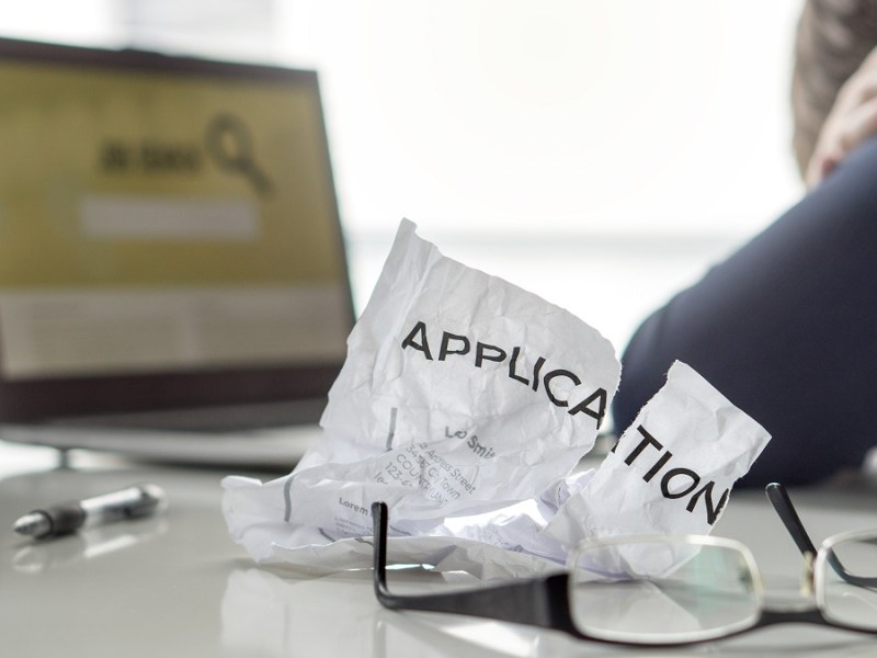 "Person with head in hands in front of computer searching for jobs. Crumpled piece of paper with the word ""application"" next to the person."