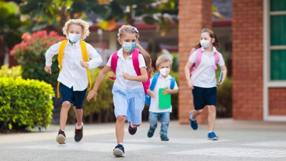 School children with face masks run into school with backpacks on