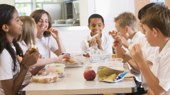 School children at a table in cafeteria eating lunch together