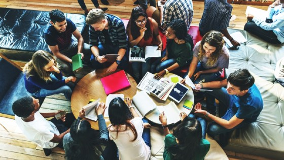 Diverse high school students sitting in a circle at a library talking to each other and looking at books and computers