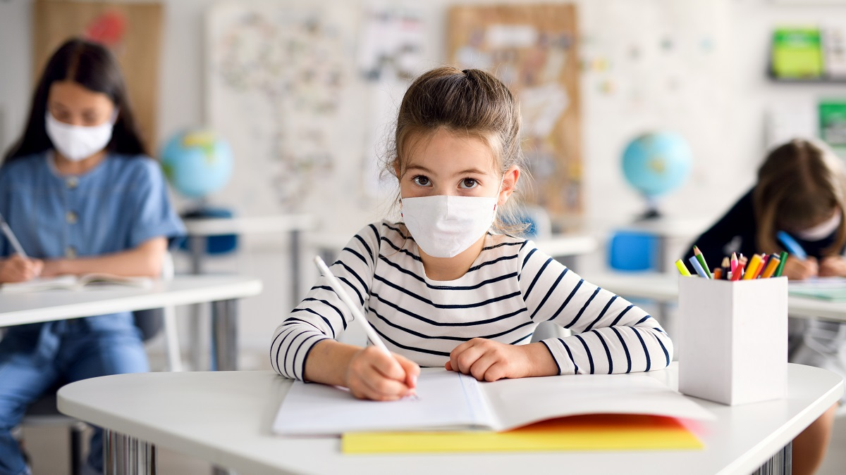 Young girl sitting at desk in classroom wearing face mask
