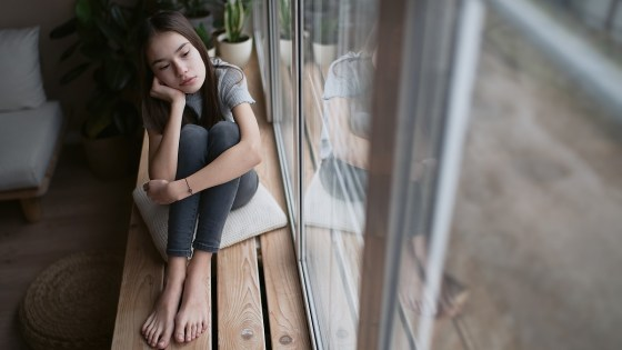 Young girl sitting by a window looking upset
