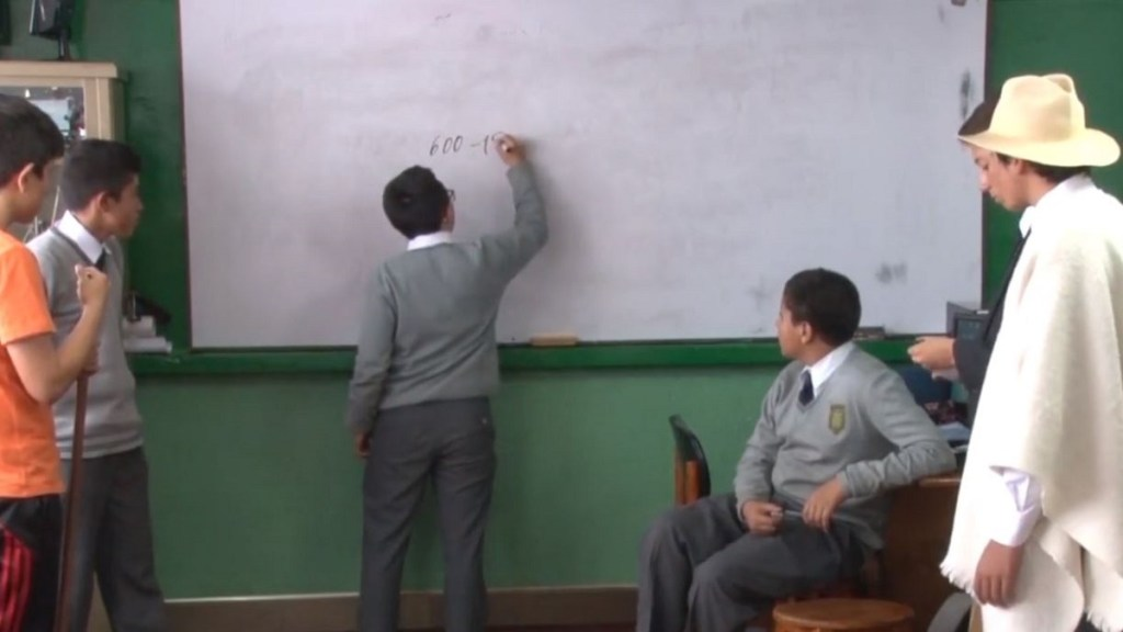 Colombian classroom scene with student writing on whiteboard while teacher and other students watch