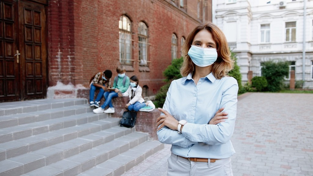 Female school principal wearing face mask with arms crossed standing outside school building with children sitting behind