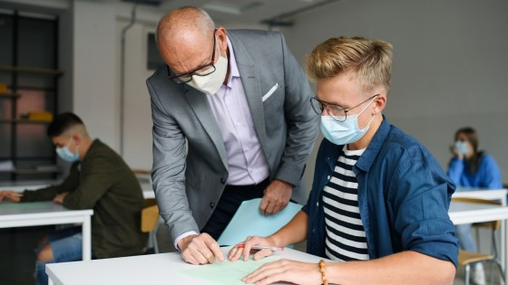 Older male teacher wearing face mask helping high school student with his work at the student's desk