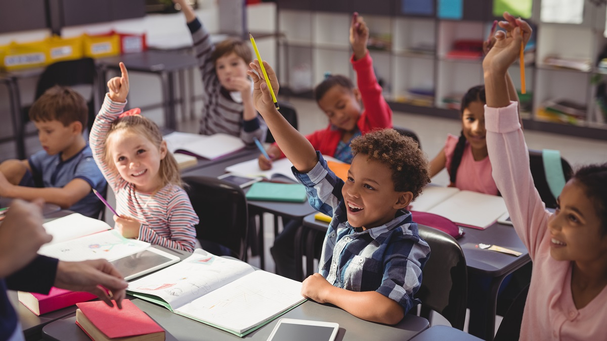 Happy children sitting in classroom with hands raised