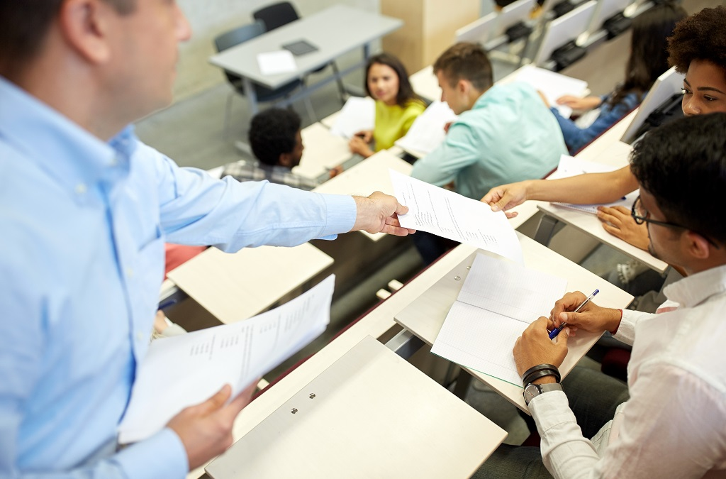 Teacher hands exam paper to student in lecture theatre