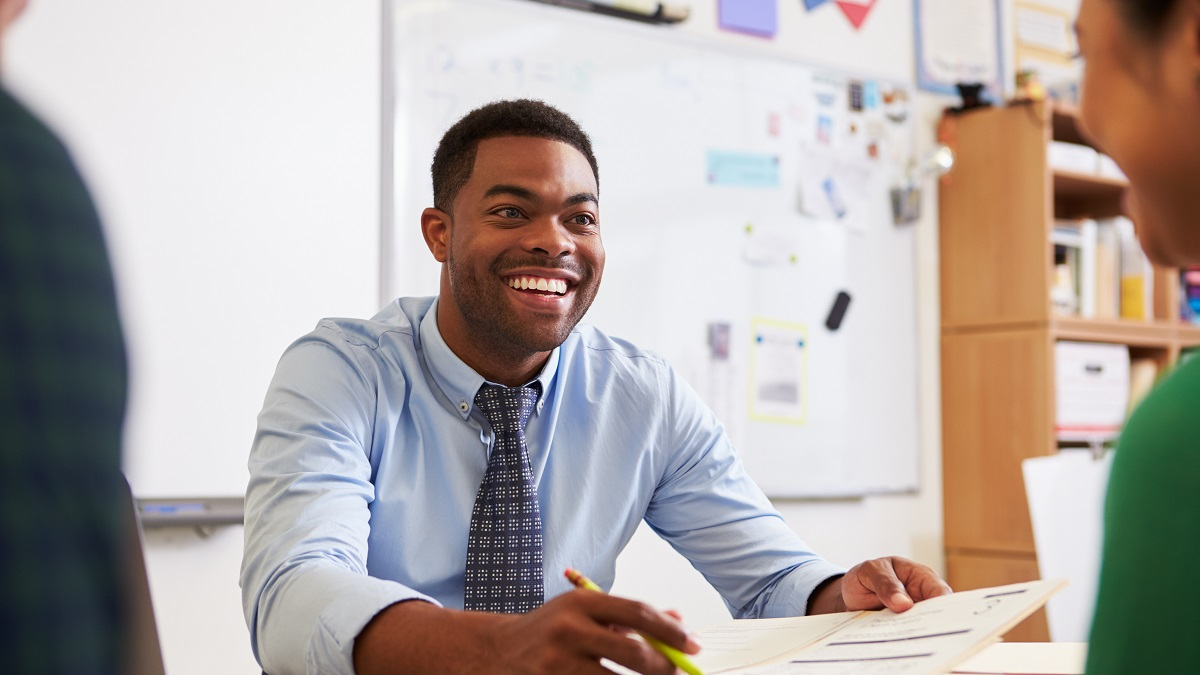Happy teacher sitting at desk in classroom discussing paper with student