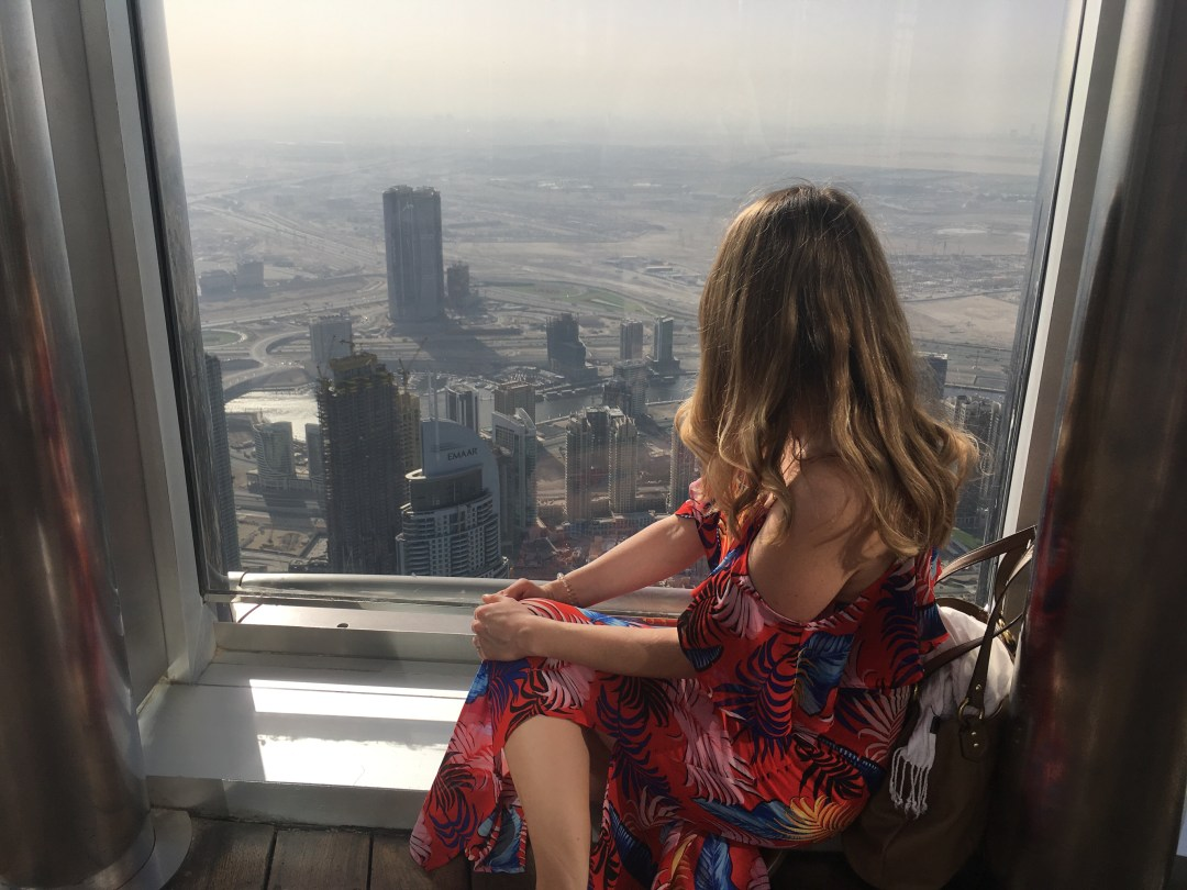 Girl wearing maxi dress looking out window at top of Burj Khalifa - what to wear in Dubai