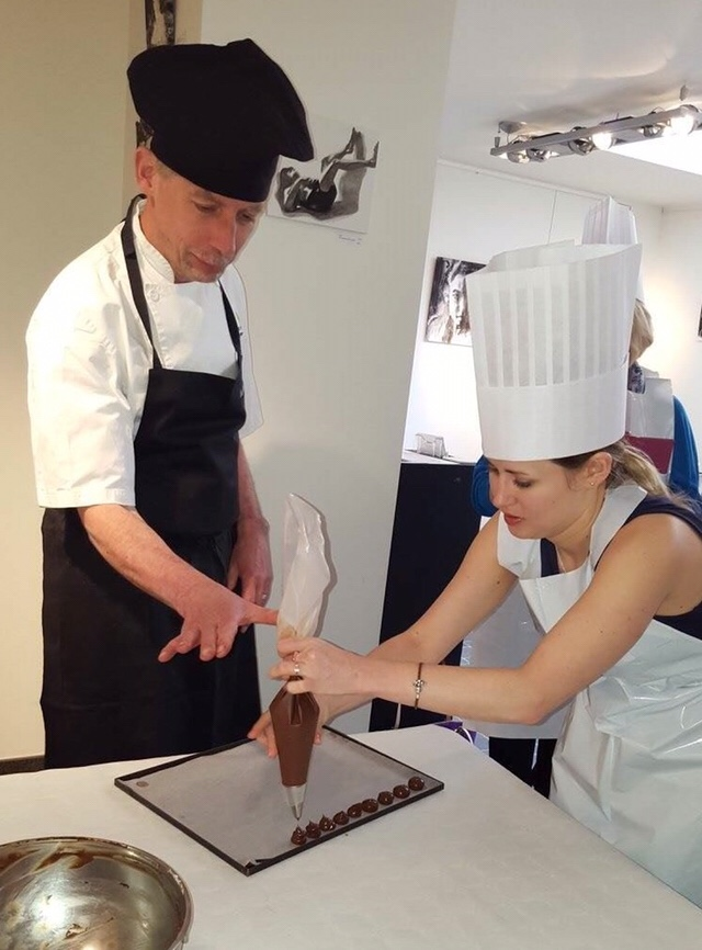 Girl pipes Belgian chocolate onto tray as part of chocolate making lesson in Ghent, Bruges