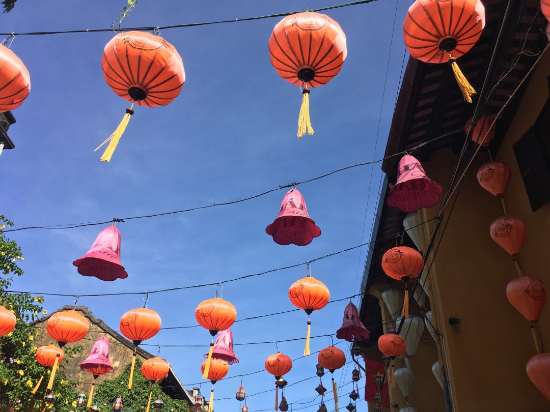 Pink and orange silk lanterns hang from the streets of Hoi An Vietnam