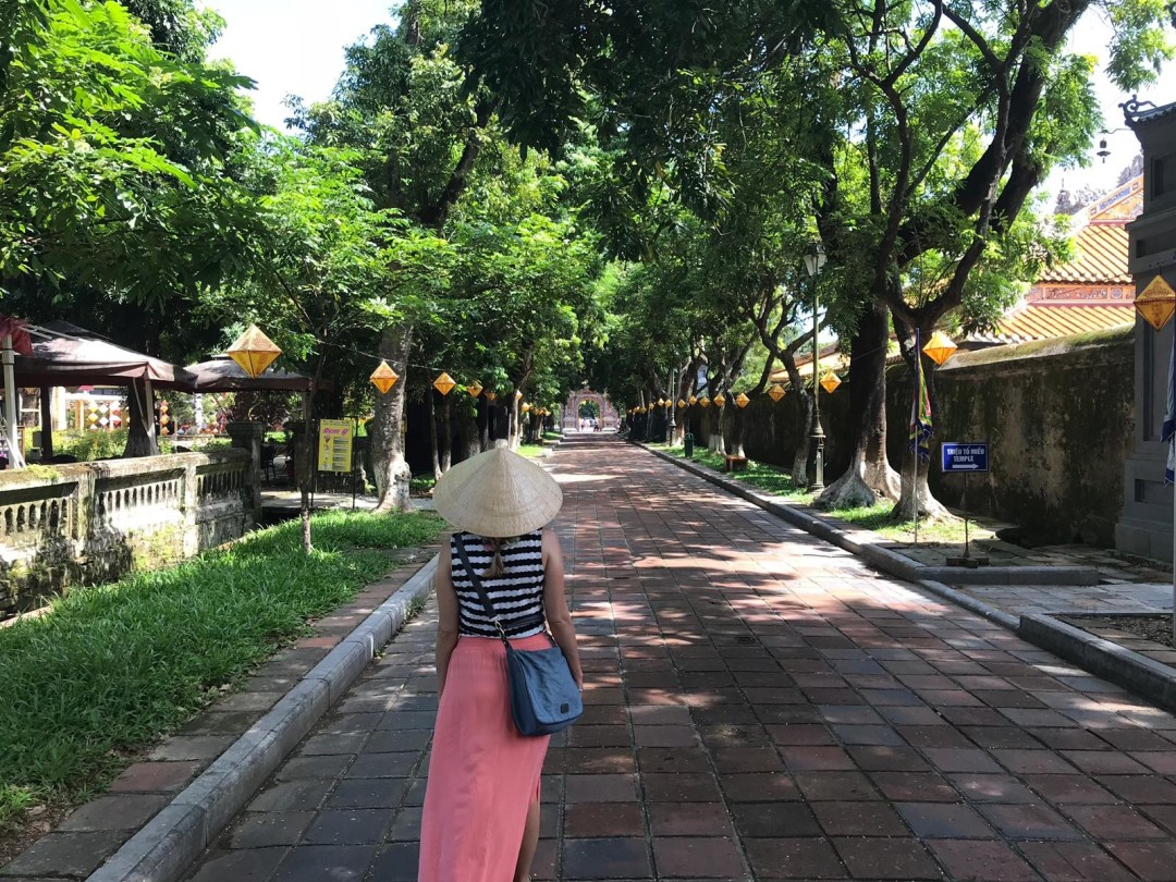 Girl in non la wanders down path lined with tropical trees and silk lanterns in Hue