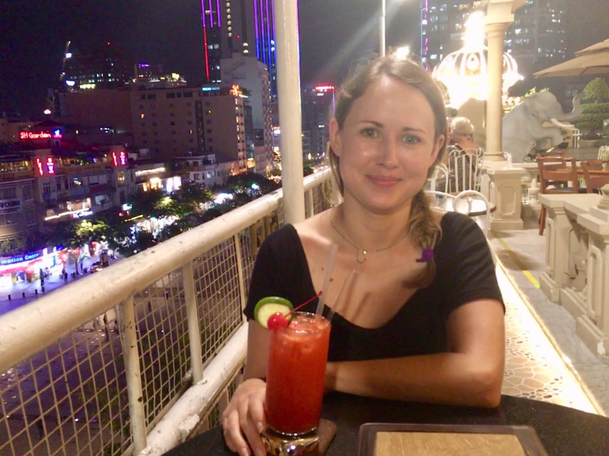 Girl drinking cocktail on rooftop bar Hotel Rex in Ho Chi Minh City Vietnam