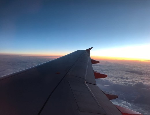 airplane wing against clear sky at sunset