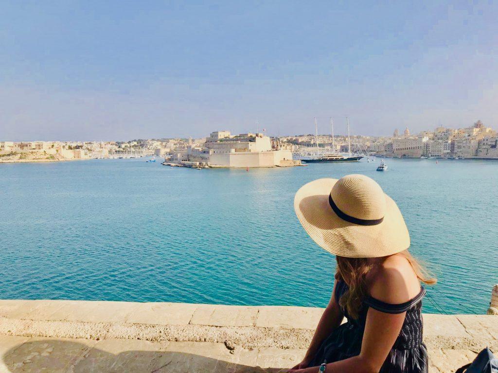 Girl sitting on Valletta walls looking across Grand Harbour towards three cities, Malta
