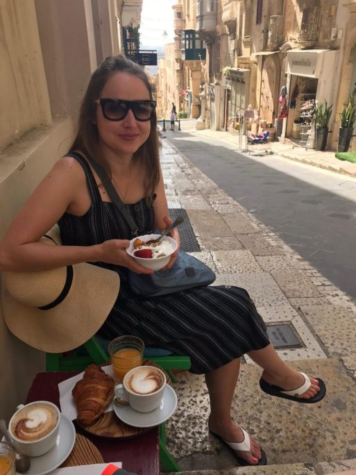 Girl sitting outside Piadina cafe on Valletta's streets with coffee, croissant and muesli