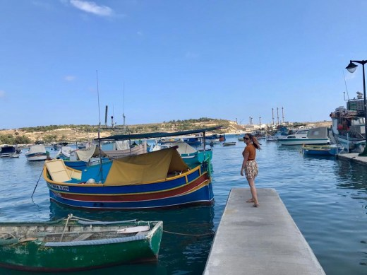 Girl stands by brightly coloured Maltese fishing boat in Marsaxlokk