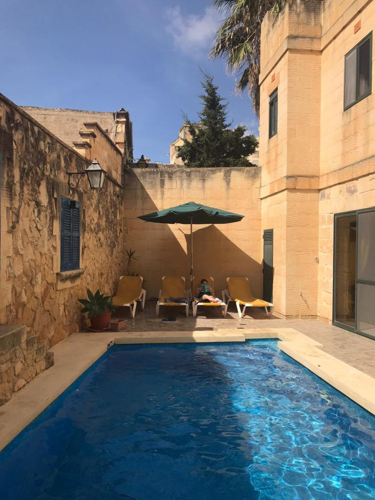 Girl reading book by pool at accommodation in Gozo,