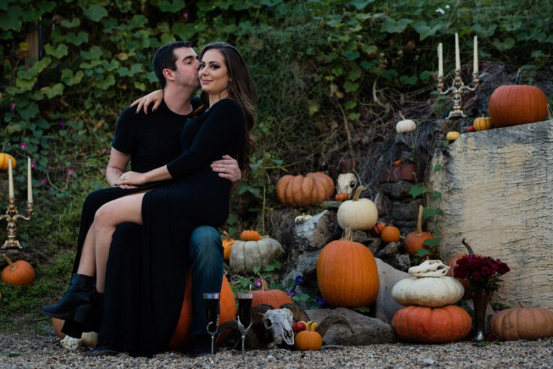 A cemetery engagement photo shoot with pumpkins, colorful smoke, and their Best Cats
