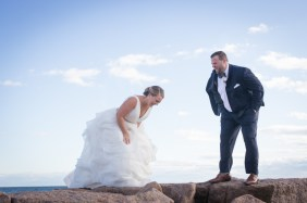 A bride and groom laughing on the rocks overlooking the ocean