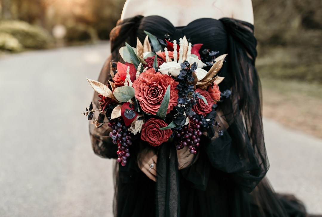 Bride in black dress, holding a large spooky bouquet of wood flowers including a faux skeleton hand and gold accents.