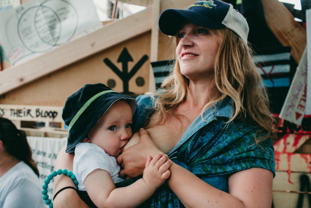 These photos of moms & babes nursing in protest of family separation will hit you right in the FEELS