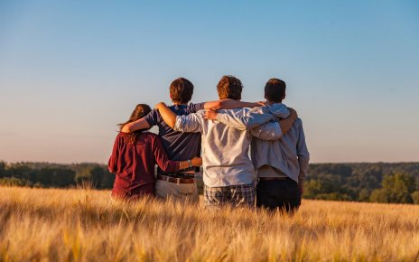 A group of teenagers sitting in a field in the sun, with their arms around one another