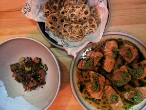 Plates on a restaurant table with food including glazed orange tuna, crispy lotus root chips, and bright orange juicy salmon
