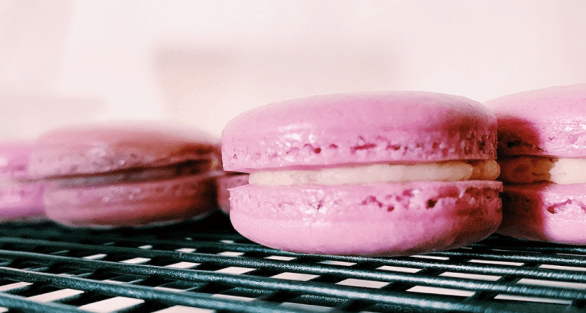 Pink macarons cooling on a wire rack tray.