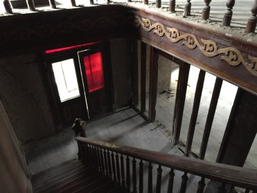 Top of the stairs, looking down at the front double doors.