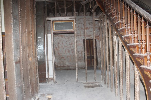 Standing at the front door, looking down the hall into the downstairs bedroom.