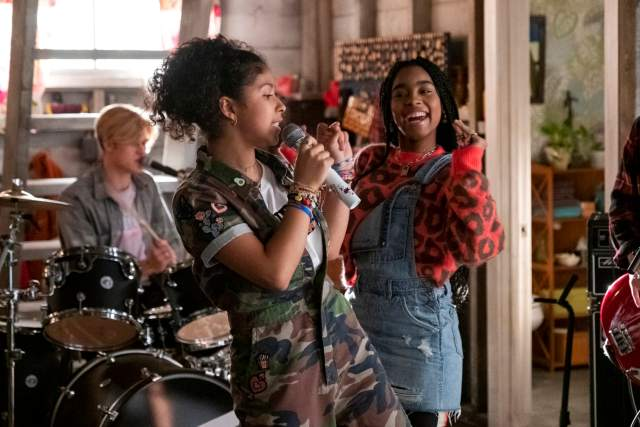 An image of Julie (Madison Reyes) and Flynn (Jadah Marie) dancing in Julie's Garage. Alex (Joyner) plays drums in the background.
