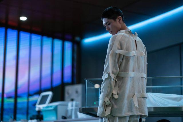 Seobok (Park Bo-gum) is standing next to a glass box. (Image courtesy of CJ Entertainment)