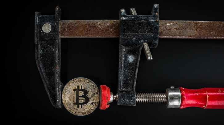 black and red caliper on gold colored bitcoin
