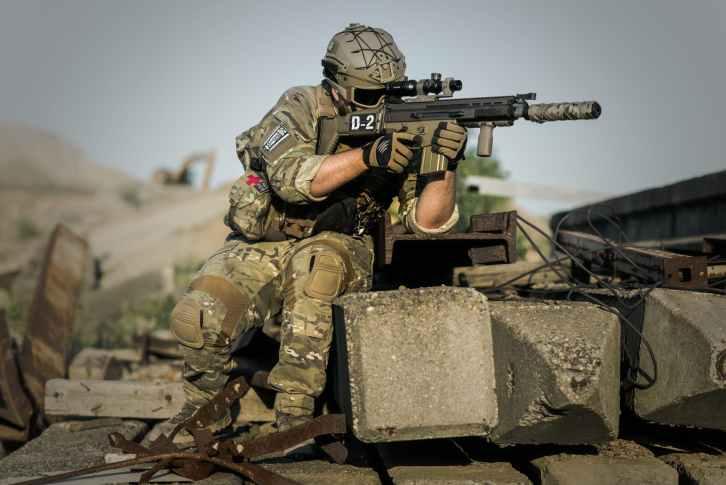 soldier near concrete pillars holding semi automatic gun with scope