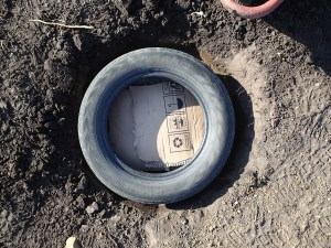 Dig  a hole, throw in a tire with some card board to keep the dirt in...