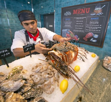 A chef positions a spiny lobster in a display case aboard the Carnival Horizon's Seafood Shack. Photo by Andy Newman/Carnival Cruise Line