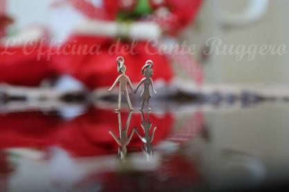 Ciondolo che si spezza e si divide in due parti: uno per la fidanzata e l'altra per il fidanzato. In argento 925. Altezza 1.5 cm circa.