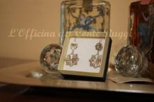 Orecchini pendenti in argento 925 Due placche agganciate a forma di stella ad 8 punte - una più piccola e una più grande - con decorazione floreale realizzata a sbalzo e cesello.