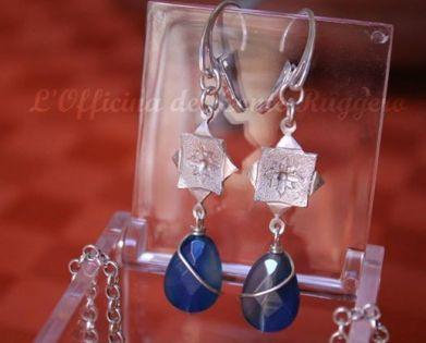 Orecchini pendenti in agata blu e argento 925 a forma di stella ad 8 punte con decorazione floreale realizzata a sbalzo e cesello. Le pietre sono avvolte da un filo in argento.
