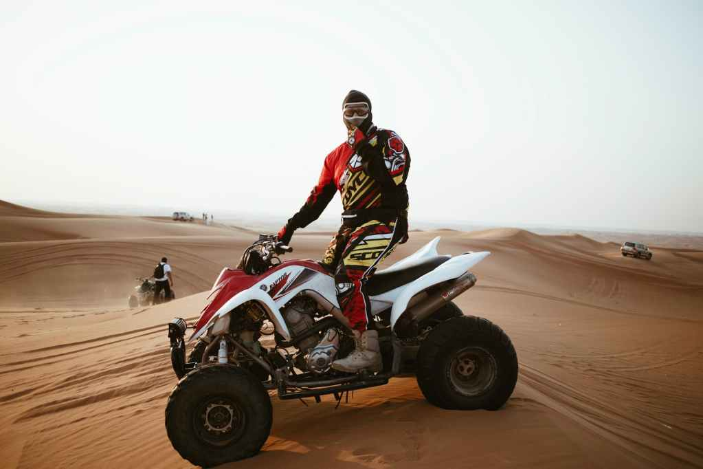 man in helmet on quad bike in desert