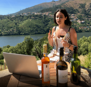 women drinking wine in front of computer