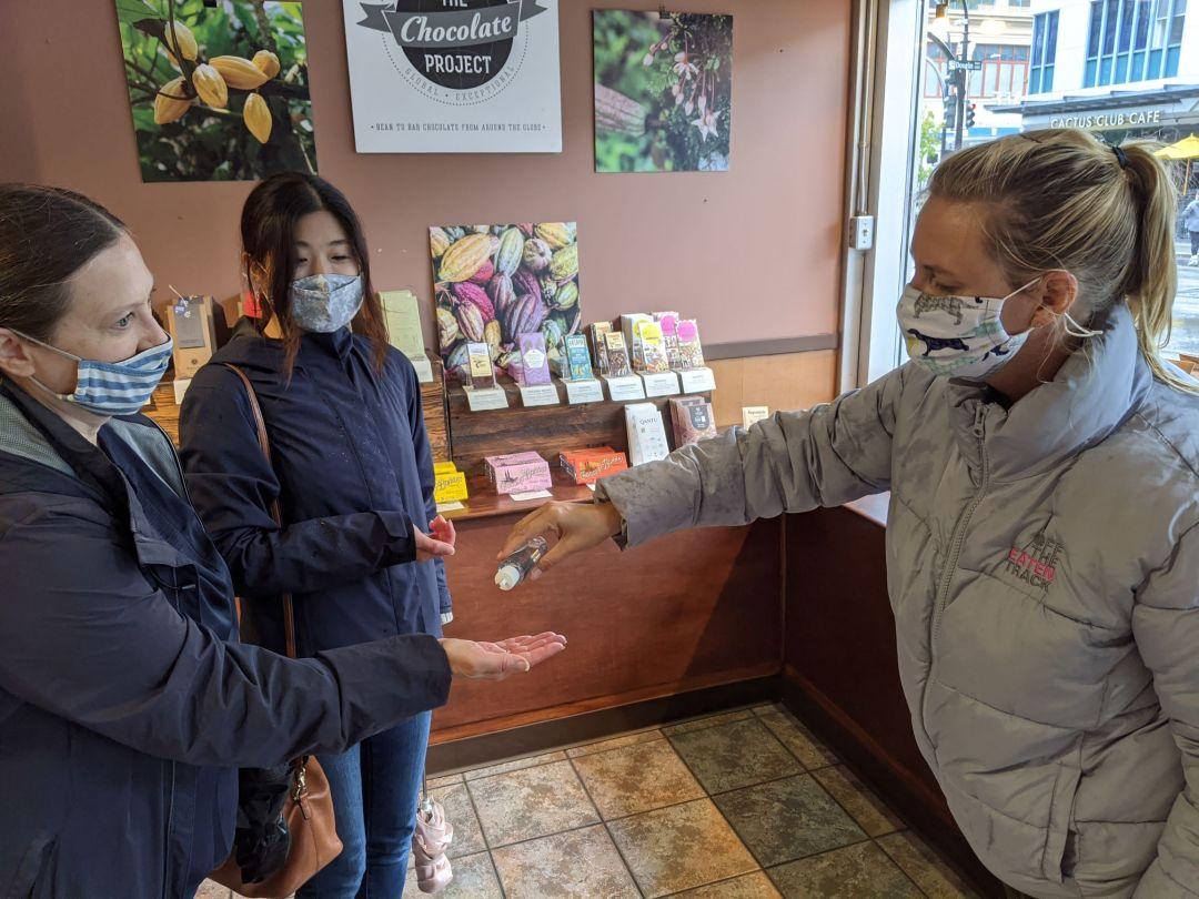 women handing out hand sanitizer