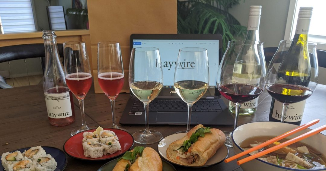 glasses of wine and food next to a computer