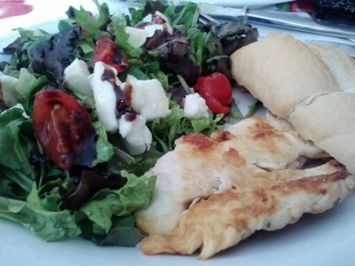 Pollo grigliato con pane e insalata mista. Grilled chicken with bread and tossed salad (the salad has mozzarella in it).