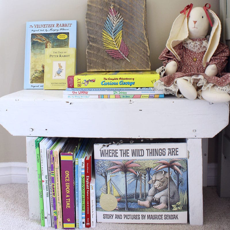 Small home library using a bench lined with children's picture books.