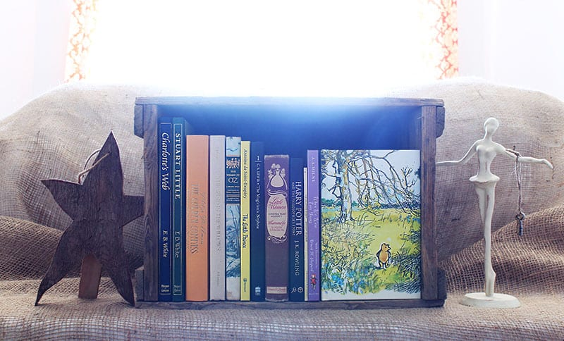 Small home library using a crate filled with classic children's and young adult novels.