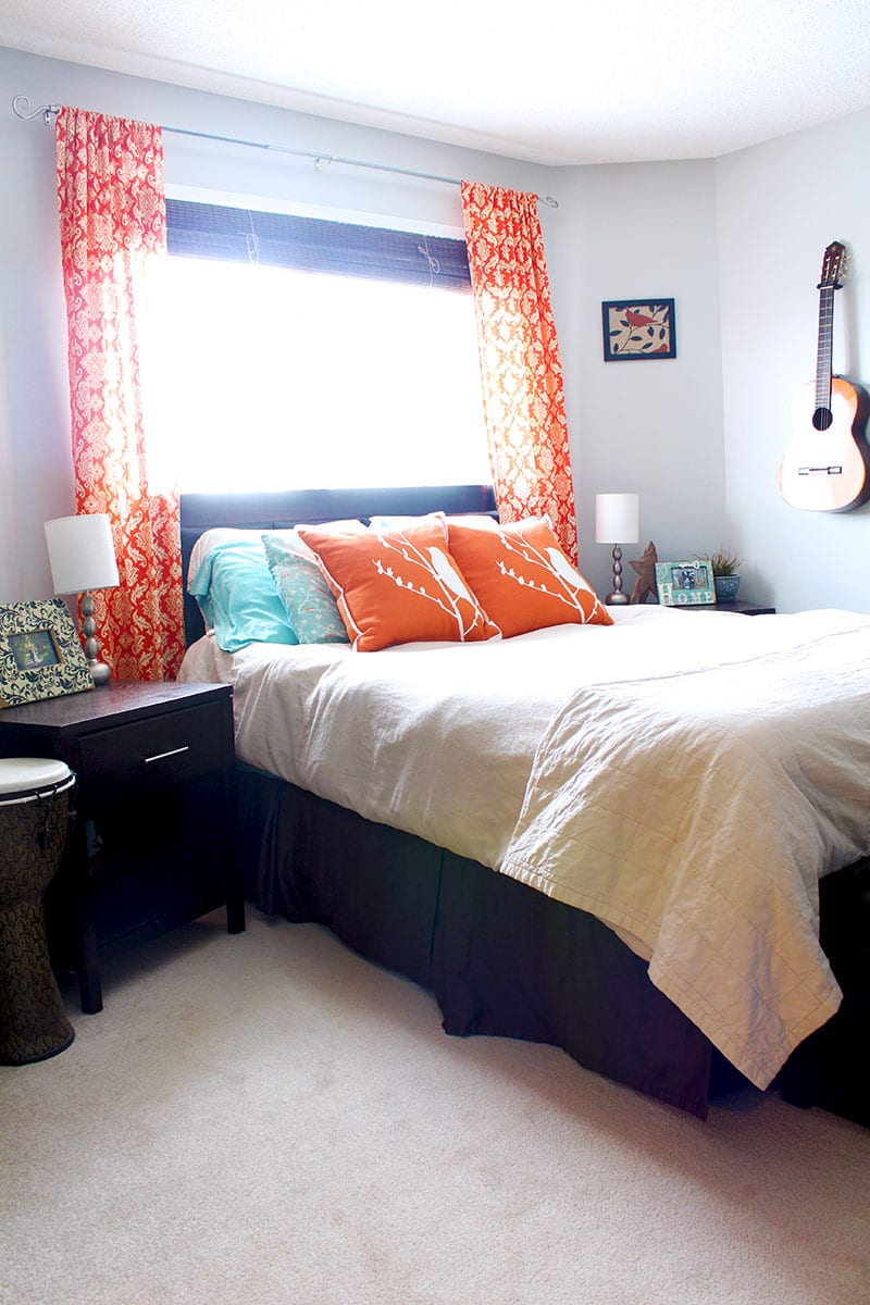 A blue and orange master bedroom with damask curtains and bird accents.