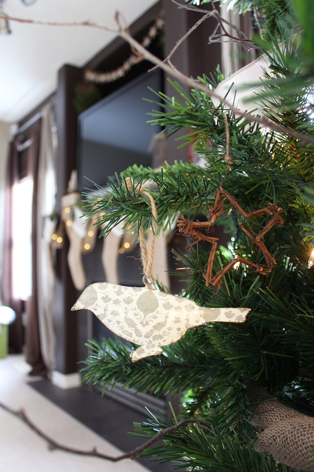 Nature inspired holiday decor featuring bird and star ornaments on a faux Christmas tree with real birch branches.